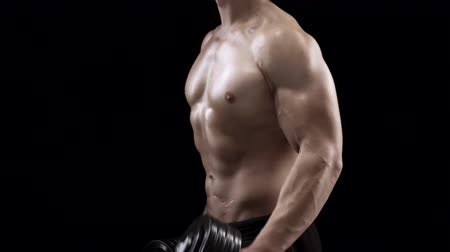 Man flexes his hands with dumbbells, training his biceps on a black background in the studio, side view Vídeos