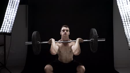 Man is doing exercises with a barbell, is engaged in a crossfit on a black background in the studio Stock Footage
