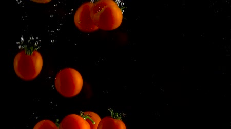 vitamina : Red tomatoes fall and float in water, black background, slow motion