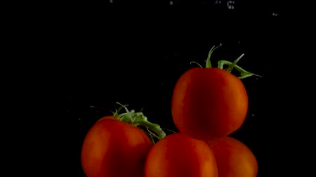 vitamina : Red tomatoes fall and float in water, black background