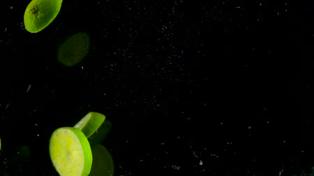 vitamina : Lime pieces fall and float in water, black background, slow motion