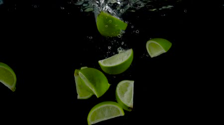 Lime pieces fall and float in water, black background