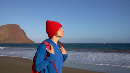 Active hiker woman walks on the beach. Caucasian young woman with backpack on Tenerife, Canary Islands, Spain