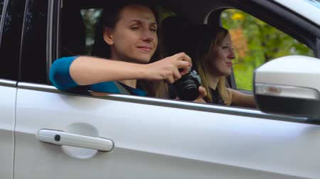 aparat : Two young women ride in a car and have fun. One of them takes a photo on a film camera. Slow motion