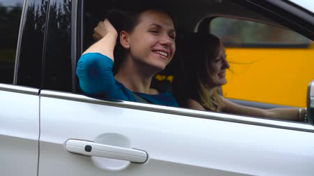 mutlu : Two young women ride in a car and have fun. Slow motion Stok Video