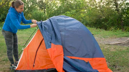Woman is putting a tourist tent in the forest