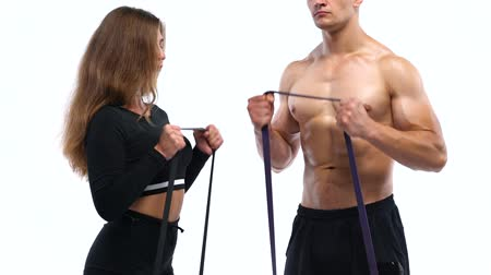 Athletic man and woman doing biceps exercises with elastic bands on a white background in studio Vídeos