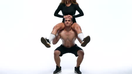 Athletic man puts a girl on his shoulders and squats with her on a white background in studio