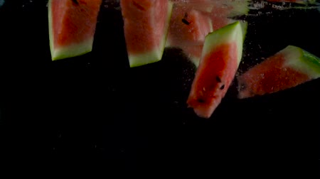 Pieces of watermelon fall and float in water, black background. Slow motion