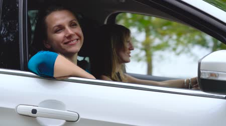 Two young women ride in a car and have fun. Slow motion Vídeos