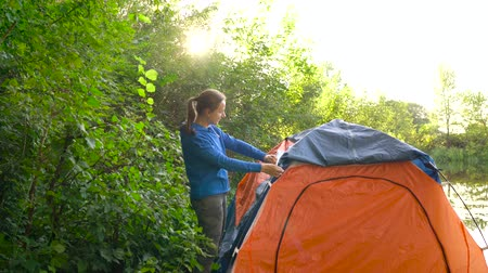 natura : Woman is putting a tourist tent on the river bank