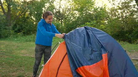 Woman is putting a tourist tent in the forest at sunset