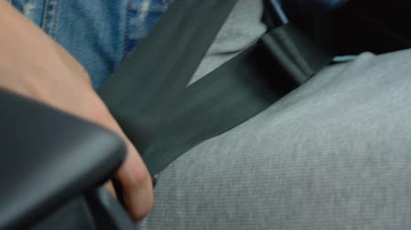 auto parking : Female hand fastening car safety seat belt while sitting inside of vehicle before driving Stock Footage
