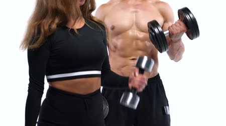 waga : Athletic man and woman flexes their hands with dumbbells, training their biceps on a white background in studio
