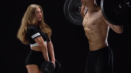waga : Athletic man and woman crouch with extra weight, training their legs and buttocks on a black background in studio Wideo