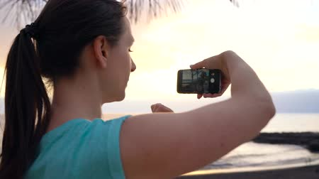 Woman taking pictures of the sunset on the promenade, Tenerife, Canary Islands, Spain