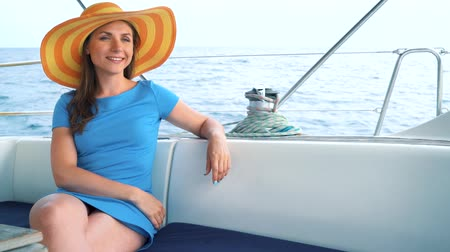iatismo : Woman in a yellow hat and blue dress girl rests aboard a yacht on summer season at ocean