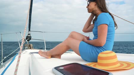 Woman in a yellow hat and blue dress rests aboard a yacht on summer season at ocean Vídeos