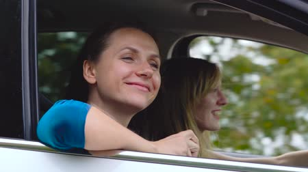 Two young women ride in a car and have fun. One of them takes a self photo on a film camera. Slow motion