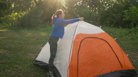 relaks : Woman is putting a tourist tent in the forest at sunset
