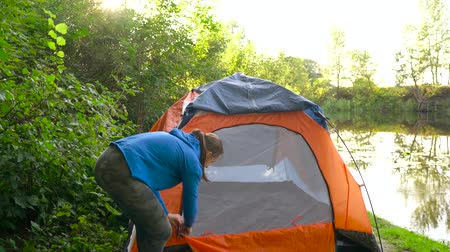 relaks : Woman is putting a tourist tent on the river bank