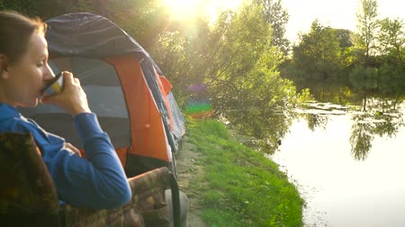 relaks : Woman is drinking tea in an armchair near a tent on the river bank