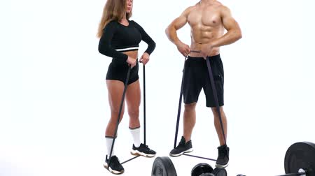 waga : Athletic man and woman doing exercise on the shoulders with elastic bands on a white background in studio