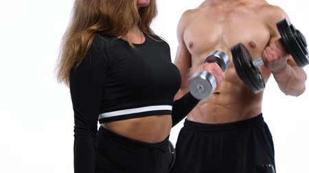 energia : Athletic man and woman flexes their hands with dumbbells, training their biceps on a white background in studio