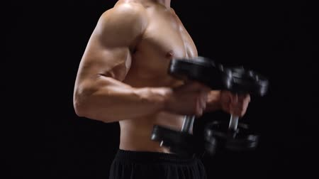 lidské tělo : Man flexes his hands with dumbbells, training his biceps on a black background in the studio Dostupné videozáznamy