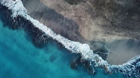 sziget : Top view of a deserted black volcanic beach. Coast of the island of Tenerife. Aerial drone footage of sea waves reaching shore Stock mozgókép
