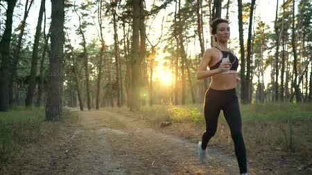 életerő : Close up of woman with headphones running through an autumn forest at sunset. Filmed at different speeds - normal and slow motion