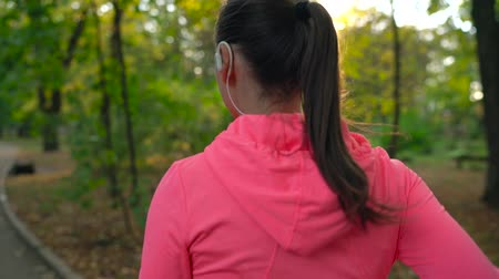 energia : Woman with wireless headphones and a smartphone chooses the music and runs through the autumn park. Slow motion