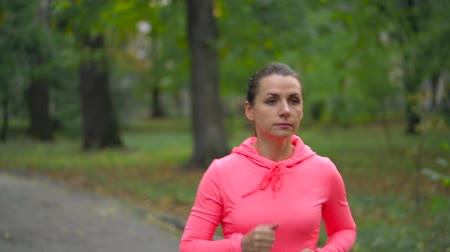 energia : Close up of woman running through an autumn park at sunset Wideo