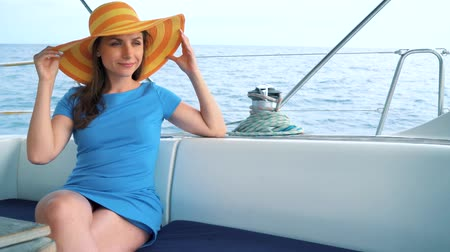 plachta : Woman in a yellow hat and blue dress girl rests aboard a yacht on summer season at ocean