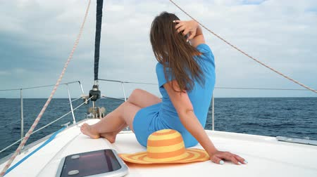 plachta : Woman in a yellow hat and blue dress rests aboard a yacht on summer season at ocean Dostupné videozáznamy