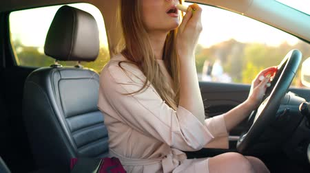 очки : Beautiful girl in in glasses paints lips in the car and check her appearance in the mirror