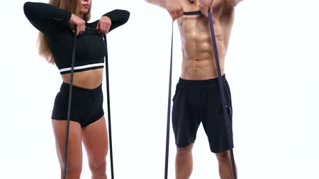 body building : Athletic man and woman doing shoulder exercises with elastic bands on a white background in studio