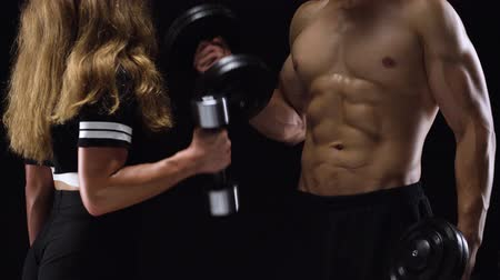 waga : Athletic man and woman flexes their hands with dumbbells, training their biceps on a black background in studio