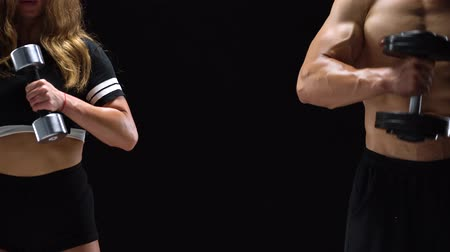 gumka : Athletic man and woman flexes their hands with dumbbells, training their biceps on a black background in studio. They stand at different edges of the frame. Center for text Wideo
