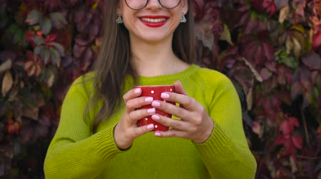 очки : Woman stretches hands with a cup of tea or coffee to the camera. Coffee break. Стоковые видеозаписи