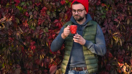 kupa : Man in a red cap with a cup in his hands drinking tea or coffee outdoors. Coffee break. Stok Video