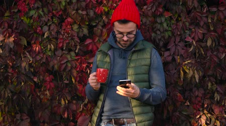 kupa : Man in a red cap with a cup in his hands is drinking tea or coffee outdoors and using a smartphone on a warm autumn day. Coffee break. Stok Video