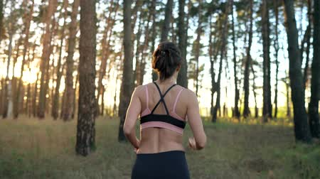 energia : Close up of smiling woman inserts headphones into ears and running through an autumn forest at sunset. Slow motion