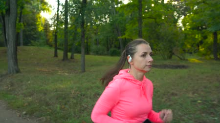 életerő : Close up of woman with wireless headphones and a smartphone running through an autumn park at sunset Stock mozgókép