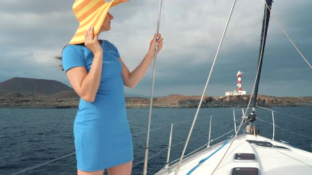 iatismo : Woman in a yellow hat and blue dress rests aboard a yacht near the lighthouse on summer season at ocean Stock Footage