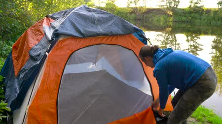 turisták : Woman is putting a tourist tent on the river bank