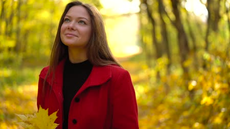 ruhák : Beautiful girl walks in the autumn forest and enjoys good weather. Slow motion Stock mozgókép