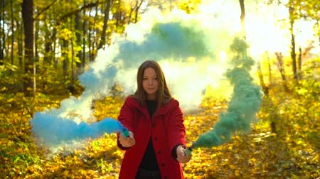 relaks : Beautiful girl in a red coat holds colored smoke in her hands and walks through the yellow autumn forest Wideo