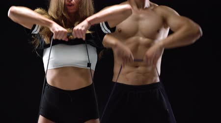 waga : Athletic man and woman doing exercise on the shoulders with elastic bands on a black background in studio