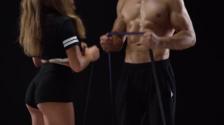 リフト : Athletic man and woman doing exercise on the biceps with elastic bands on a black background in studio